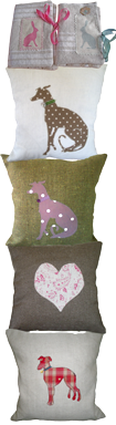 A pair of hare cushion covers, 3 lurcher cushions and a heart cushion, on different colour backgrounds, some light, some dark